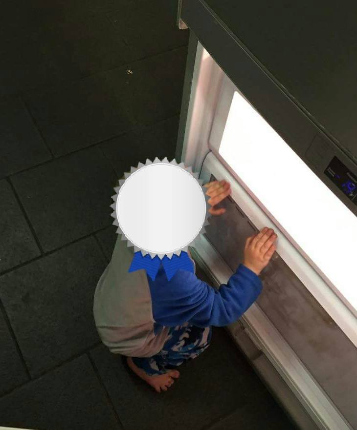one of the six rescued kids in front of fridge.jpg